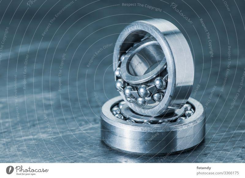 Two spherical roller bearings on slate blue toned Industrie Handwerk Technik & Technologie Metall Stahl Kugel drehen stehen außergewöhnlich rund blau grau