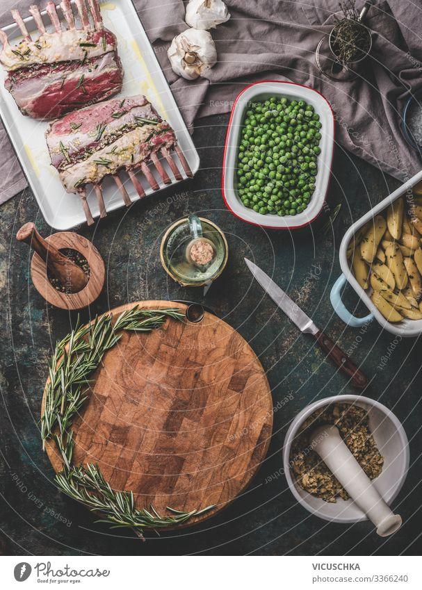 Hintergrund zum Thema Fleischwaren. Kochzubereitung mit rohem Lammfleisch, grünen Erbsen, Backkartoffeln und Rosmarinbrotkruste auf rustikalem Tisch mit leerem Schneidebrett. Ansicht von oben. Lamm-Karren