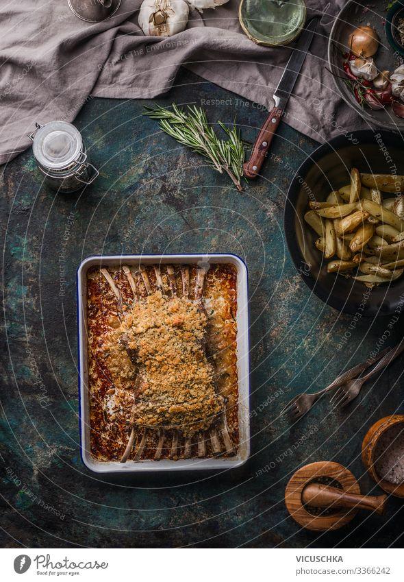 Gebratene Lammkarrees mit Kruste auf dunklem, rustikalem Tisch, Draufsicht. Fleischnahrung oben Barbecue grillen Knochen hacken gekocht Essen zubereiten