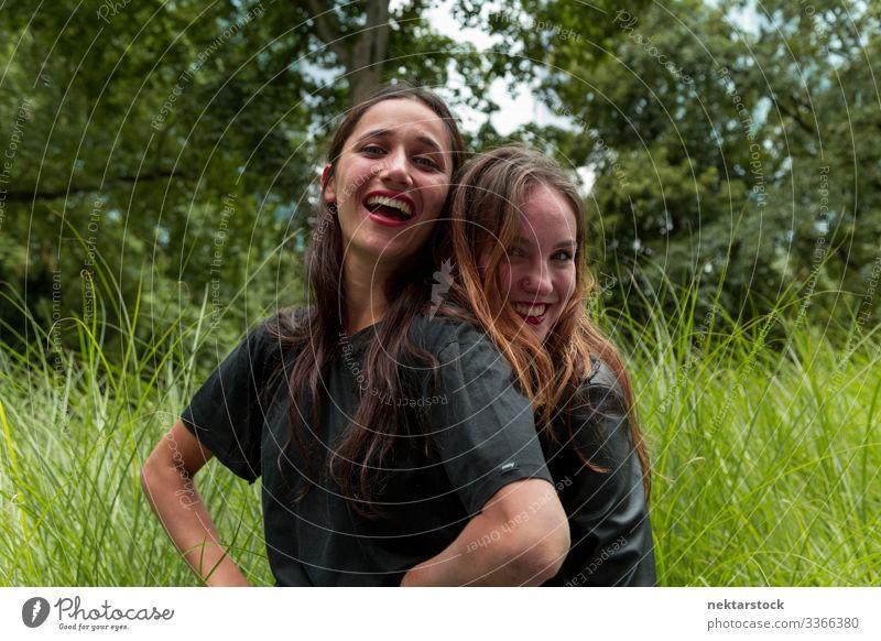 Porträt von zwei hübschen jungen Frauen, die sich im Freien umarmen und lächeln junger Erwachsener Tagesschönheit schöne Frauen natürliche Schönheit