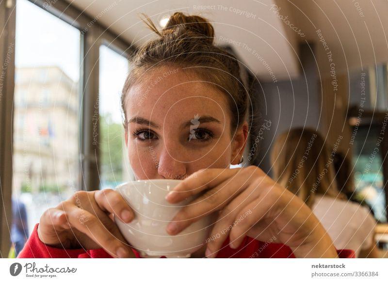 Junge Frau trinkt aus Kaffeetasse und schaut in die Kamera Mädchen junger Erwachsener Gesicht Tag weibliche Schönheit schöne Frau natürliche Schönheit 1 Mensch