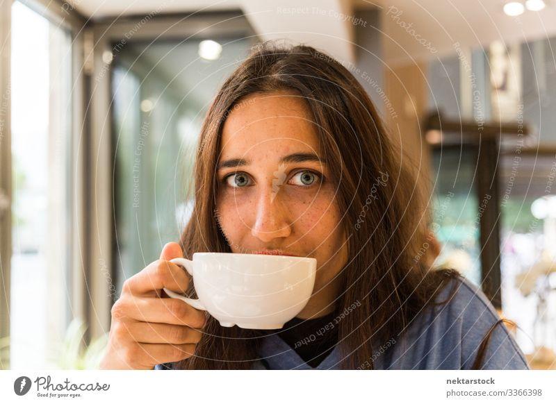 Junge Frau mit Kaffeetasse auf den Lippen schaut in die Kamera Porträt gebräunte Haut hell gefärbte Augen Tasse Becher trinken Getränk Porzellan