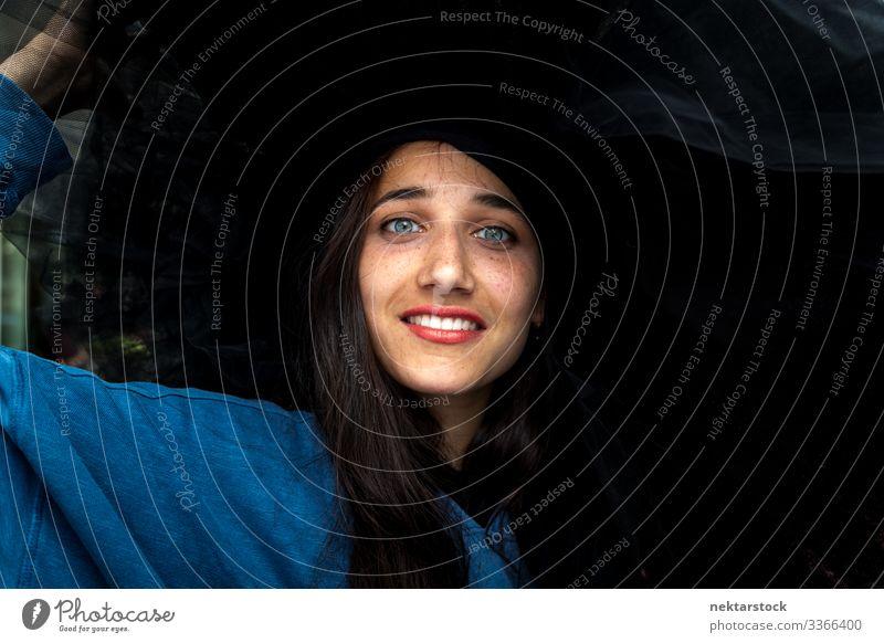 Schöne Aufnahme einer jungen Frau mit großem schwarzen Hut Mädchen Schönheitsschuss Lächeln Porträt hell gefärbte Augen gebräunte Haut gebräunter Teint Gesicht