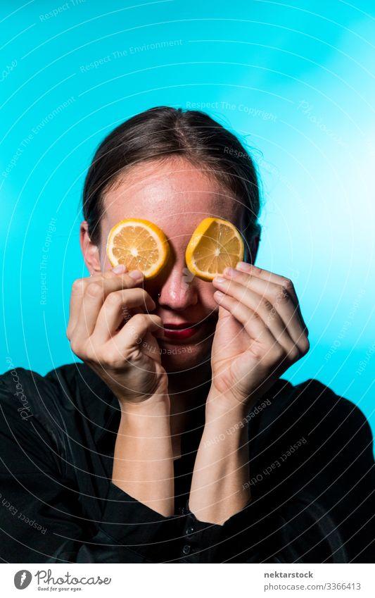 Junge Frau mit Zitronenscheiben über den Augen auf blauem Hintergrund Scheibe deckend Mädchen Überfall Konzept Minimalismus Zitrusfrüchte Frucht frisch Frische