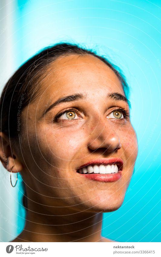 Lächelndes Gesicht einer jungen indischen Frau auf blauem Hintergrund haselnussbraune Augen Mädchen Zahnfarbenes Lächeln junger Erwachsener weibliche Schönheit
