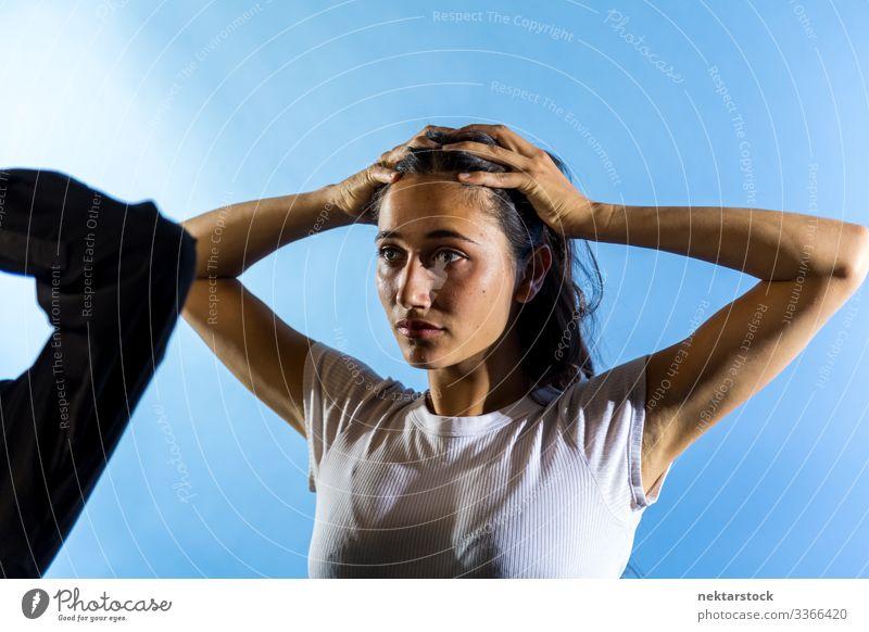 Junge Frau mit Händen auf dem Kopf im Studio mit blauem Hintergrund Hände auf dem Kopf Mädchen junger Erwachsener weibliche Schönheit schöne Frau