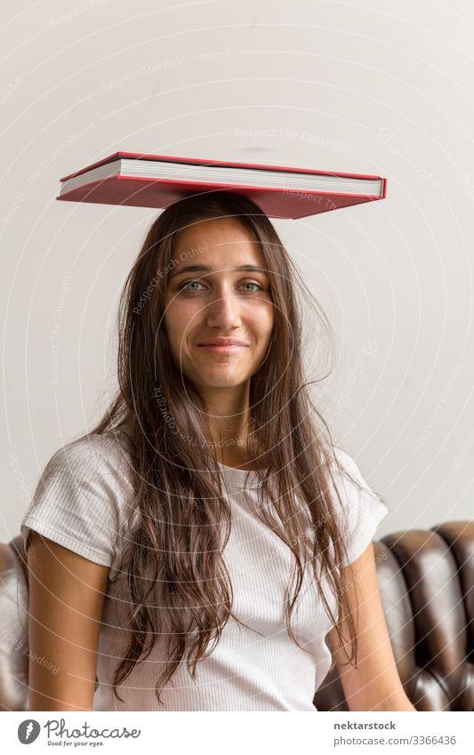 Porträt einer jungen Frau mit Buch auf dem Kopf Mädchen junger Erwachsener Jugendkultur Tag urban weibliche Schönheit schöne Frau natürliche Schönheit