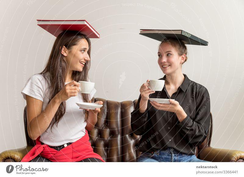 Zwei junge Frauen balancieren Bücher über den Kopf und halten Kaffeetassen, die Augenkontakt herstellen die sich gegenseitig ansehen Mädchen junger Erwachsener
