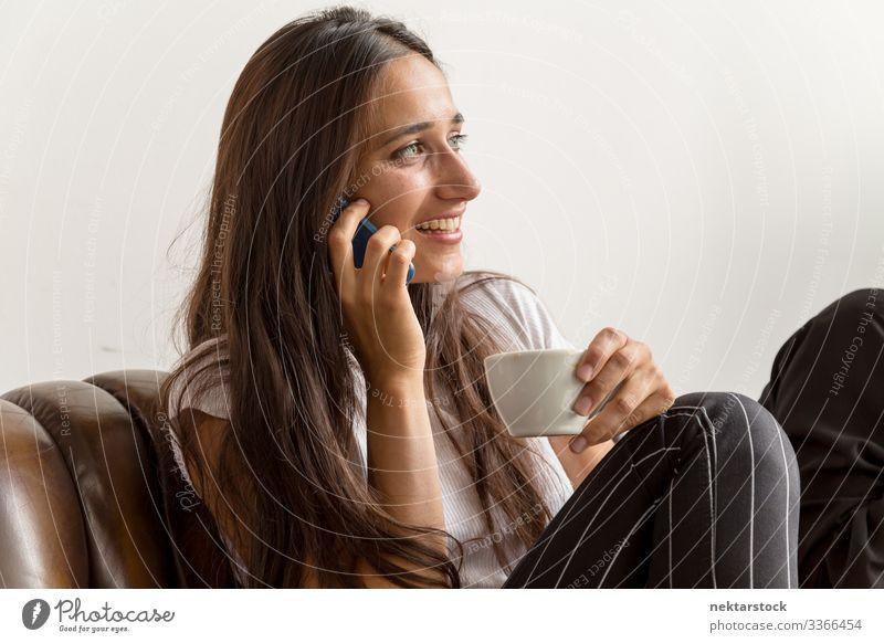 Junge Frau spricht am Telefon und hält Kaffeetasse Telefongespräch Lächeln am Telefon sprechen Mädchen junger Erwachsener Tag natürliche Schönheit reales Leben