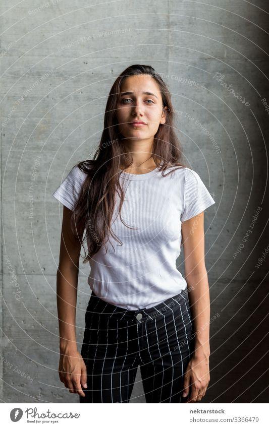 Junge Frau vor einer Betonmauer im Inneren Mädchen junger Erwachsener Porträt ernst in die Kamera schauen mittlere Aufnahme schöne Frau natürliche Schönheit