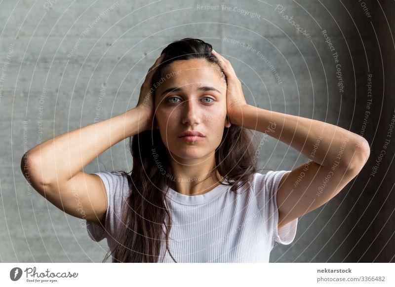 Junge Frau mit Händen an den Schläfen Mädchen junger Erwachsener Porträt Hände auf dem Kopf ernst in die Kamera schauen mittlere Aufnahme schöne Frau