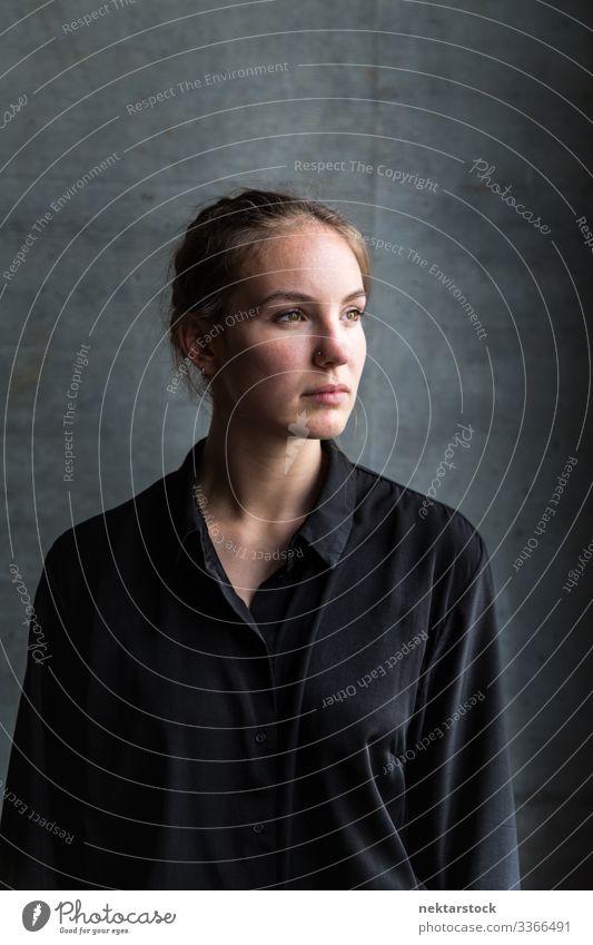 Porträt einer jungen kaukasischen Frau, die mit gedrehtem Kopf wegschaut Mädchen junger Erwachsener schöne Frau natürliche Schönheit braune Haare 1 Mensch