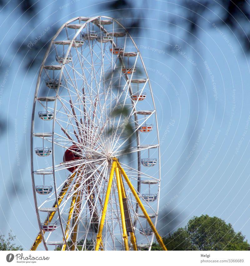 Riesenrad auf einem Jahrmarkt Freizeit Tag Himmel Spaß Karussell Fahrgeschäft rund Außenaufnahme groß hoch blau weiß gelb Attraktion Schausteller Frühling