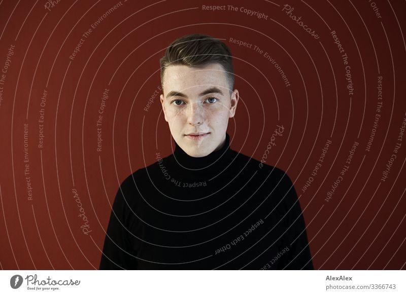 Junger Mann vor einer roten Wand Lifestyle Stil schön Wohlgefühl Raum Jugendliche 18-30 Jahre Erwachsene Pullover blond kurzhaarig rote Wand Blick stehen