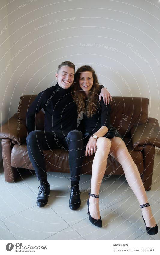 Junger Mann und junge Frau sitzen auf einer braunen Leder- Couch innig zusammen und lächeln Lifestyle Stil Freude schön harmonisch Häusliches Leben Sofa Raum