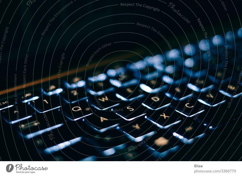 Eine blau leuchtende Laptop Tastatur mit weißen Buchstaben im dunkeln mit viel Schwarz drumherum Computer Notebook Business Technik & Technologie edel Abend
