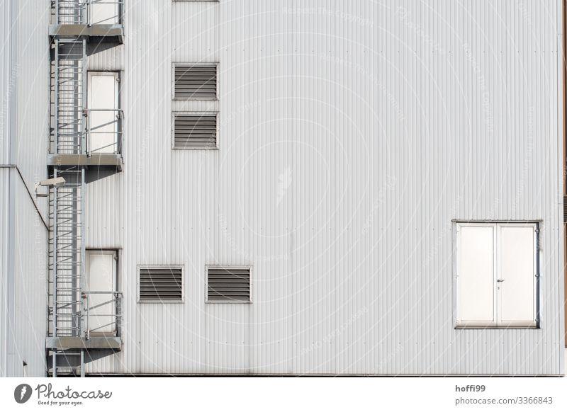 Industriefassade mit Notausgang, Lamellen und Lüftungsklappen industriell Industrielle Fassade Treppe Metall Außenaufnahme Industriebetrieb Architektur