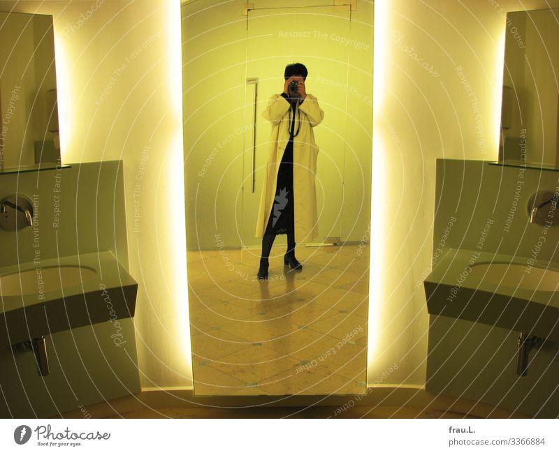 Waschraum Mensch feminin Frau Erwachsene 1 45-60 Jahre Mantel Stiefel schwarzhaarig kurzhaarig stehen außergewöhnlich gelb Spiegel Waschhaus Toilette Museum
