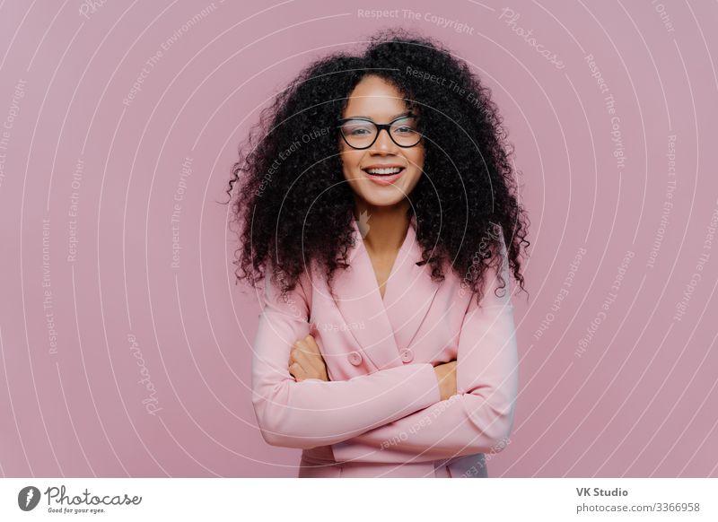 Vergnügte kraushaarige Frau trägt eine optische Brille elegant Freude Glück Haare & Frisuren Gesicht Mensch Erwachsene Bekleidung Anzug Jacke Afro-Look stehen