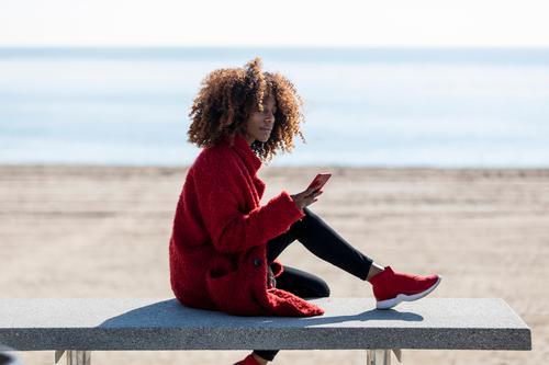 Schöne Afro-Frau sitzt an der Küste und benutzt ein Mobiltelefon Stil Glück schön Strand Telefon PDA Mensch feminin Junge Frau Jugendliche Erwachsene 1