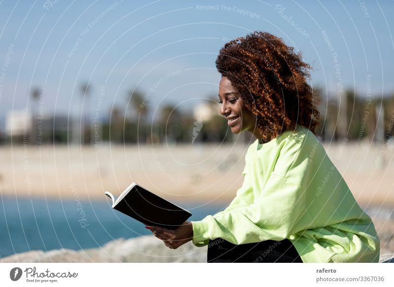 Seitenansicht einer Afro-Frau, die am Ufer sitzt und ein Buch liest Lifestyle Stil schön lesen Meer Mensch feminin Junge Frau Jugendliche Erwachsene 1