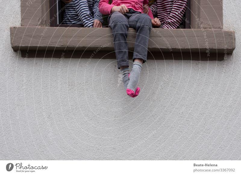 Kinder sitzen am offenen Fenster Fenstersims Farbfoto Außenaufnahme Haus Fensterrahmen Fassade Fensterbrett Füße Socken Licht Textfreiraum unten Ringelpulli