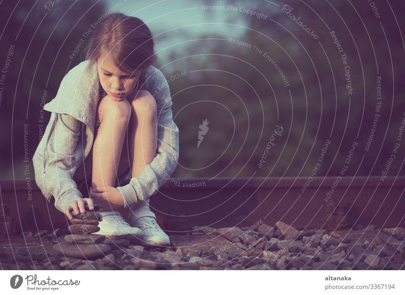 Porträt eines jungen, traurigen Mädchens, das tagsüber im Freien auf der Bahn sitzt. Konzept der Trauer. Gesicht Kind Mensch Frau Erwachsene