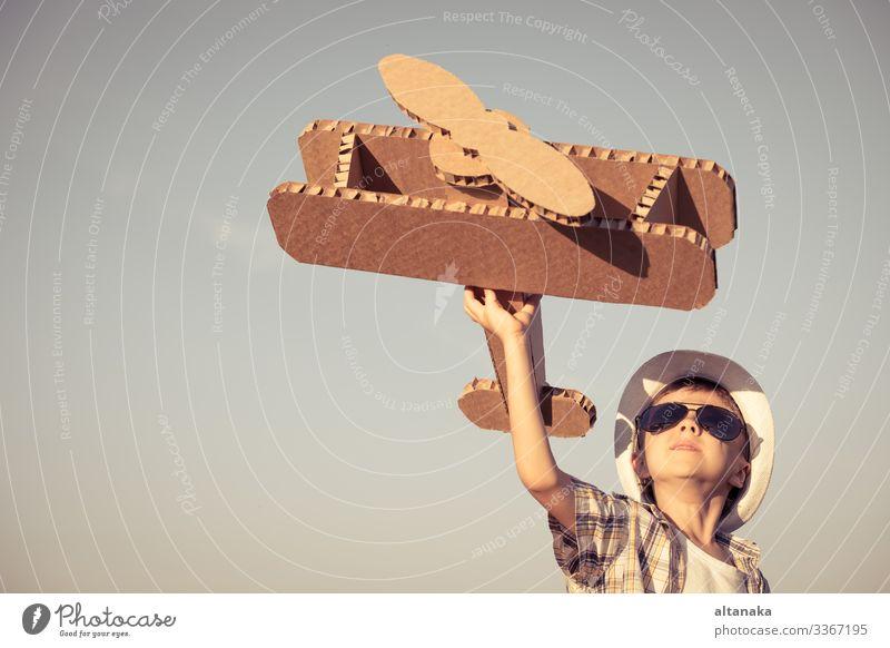 Kleiner Junge spielt tagsüber im Park mit einem Spielzeugflugzeug aus Pappe. Konzept des glücklichen Spiels. Kind hat Spaß im Freien. Lifestyle Freude Glück