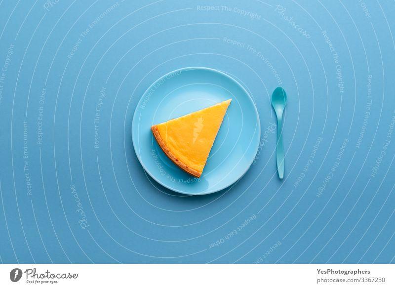 Käsekuchenscheibe auf blauem Teller. Ein Stück Käsekuchen Kuchen Dessert Süßwaren Frühstück Mittagessen lecker süß gelb Tradition obere Ansicht Backwaren