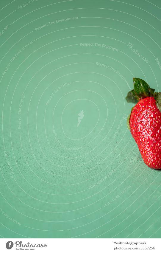 Eine Erdbeere auf grünem Tisch. Teil einer Nahaufnahme einer Erdbeere Frucht Dessert Bioprodukte Vegetarische Ernährung Diät frisch natürlich niedlich süß rot
