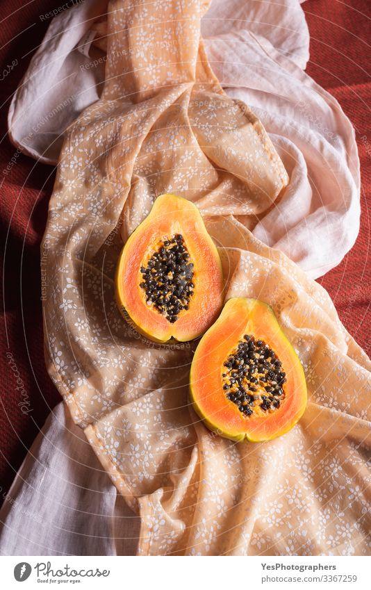 Reife Papayafruchthälften auf orangefarbenen Tischdecken. Frucht Dessert Bioprodukte exotisch Gesunde Ernährung obere Ansicht farbenfroh halbieren Diätnahrung