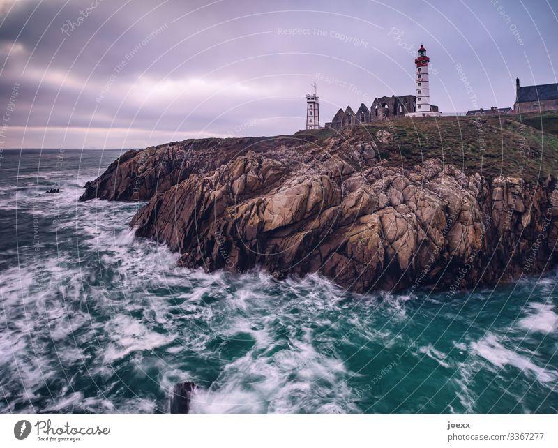 Leuchtturm an Bretonischer Felsküste mit Wellen und Meer Weitwinkel Außenaufnahme Farbfoto Idylle Horizont Hoffnung Fernweh Heimweh ruhig weiß braun blau