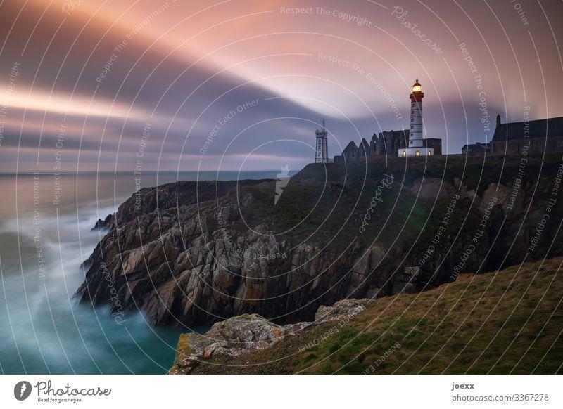 Leuchtturm an felsiger Steilküste, Langzeitbelichtung blau Felsen Wellen Schönes Wetter Himmel Küste Meer Horizont Farbfoto mehrfarbig Außenaufnahme Wolken