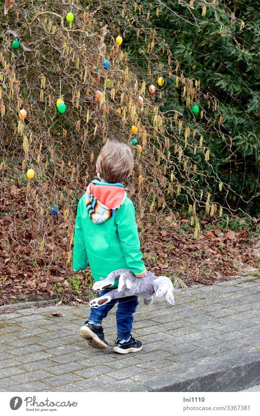 Osterspaziergang II Kind Junge 1 Mensch 3-8 Jahre Kindheit Pflanze Sträucher Haselnuss Bewegung Blick Neugier mehrfarbig Ostern Osterei Außenaufnahme