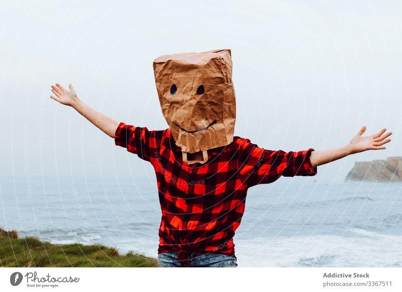 Person mit Papiertüte auf dem Kopf, die an Land springt Kunststoff Paket Ökologie Tüte Konzept Umwelt gestikulieren Zeichen Natur Verschmutzung Tasche