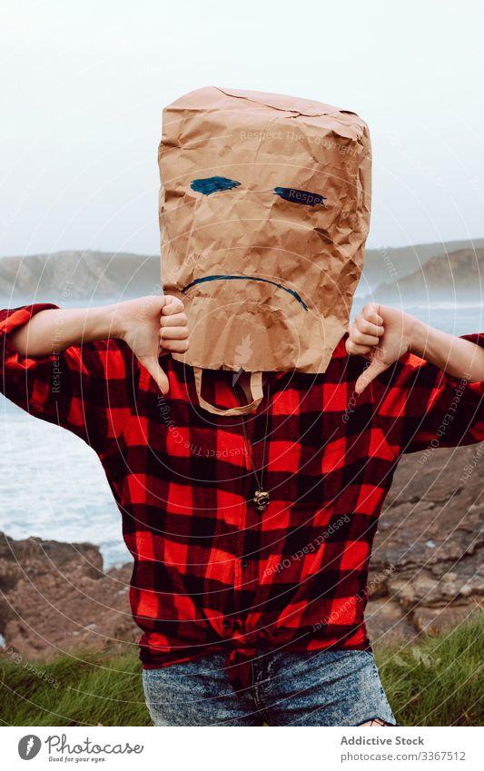 Person mit Papiertüte auf dem Kopf, die den Daumen nach unten zeigt Paket Ökologie Tüte Konzept Missbilligung nicht mögen nicht einverstanden sein Umwelt