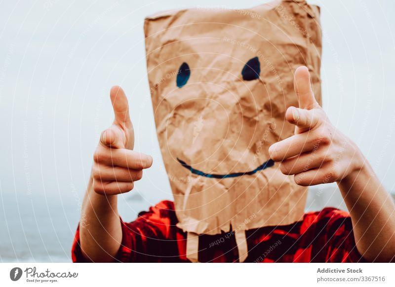 Person mit Papiertüte am Kopf, die auf die Kamera zeigt Kunststoff Paket Ökologie Tüte Konzept Zeigen Umwelt gestikulieren Zeichen Natur Verschmutzung Tasche