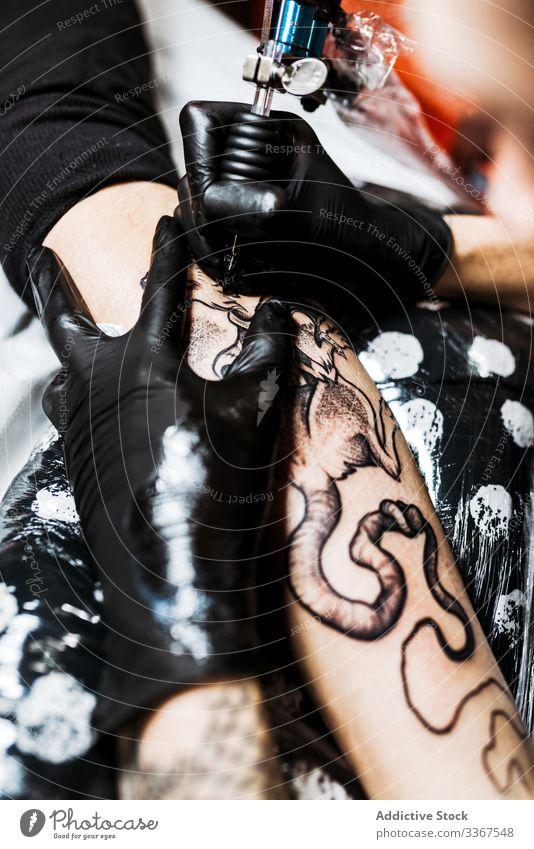 Anonymer Kropfentätowierer, der mit dem Kunden im Salon arbeitet Tätowierer Klient Mann Arbeit Tattoo Werkzeug stylisch Subkultur Künstler Kultur Meister