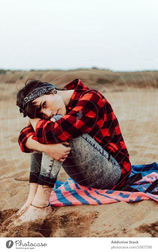 Nachdenkliche Hipster-Frau sitzt am Sandstrand Strand besinnlich sitzen ernst jung sich[Akk] entspannen nachdenklich MEER lässig Meer Beobachtung Denken rot