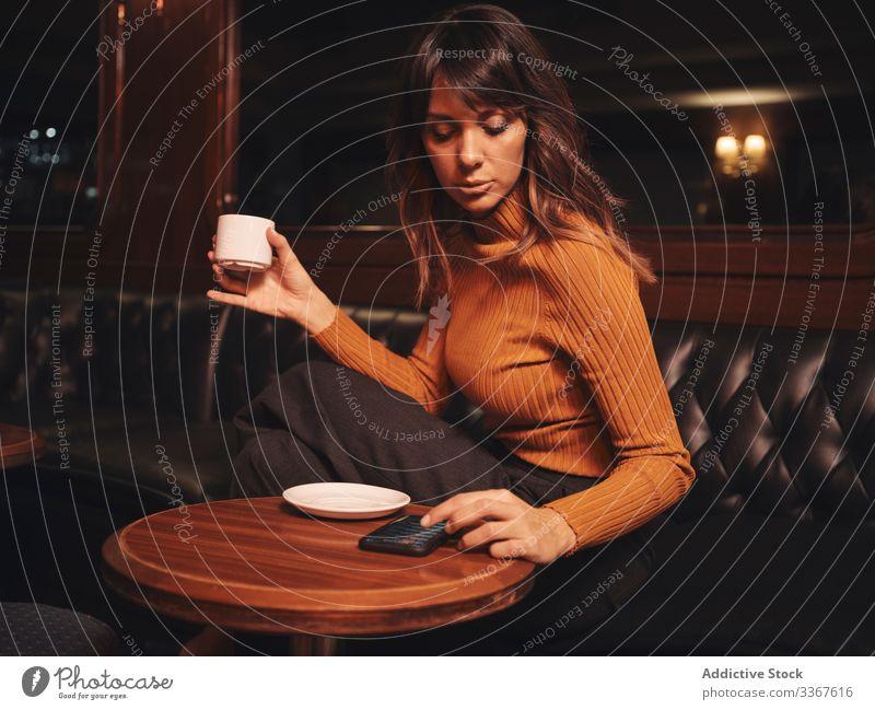 Nachdenkliche Frau trinkt Kaffee und blättert mit ihrem Smartphone bei Tisch trinken Browsen bequem benutzend Apparatur Gerät stylisch Leder elegant