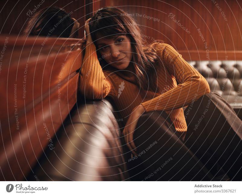 Romantische Frau auf Sofa sitzend und in der Hand gelehnt im Cafe romantisch gemütlich träumend Denken sich[Akk] entspannen Mode Liege bequem Model schwarz Dame