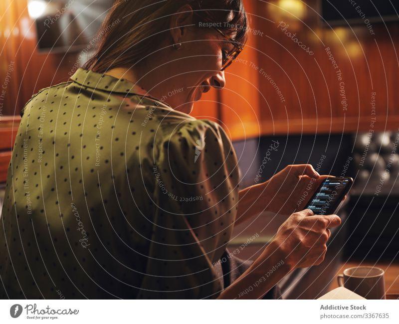 Frau mit Brille surft auf Smartphone und sitzt auf dem Sofa Browsen bequem benutzend Apparatur Gerät stylisch Leder elegant nachdenklich Mode Dame trendy