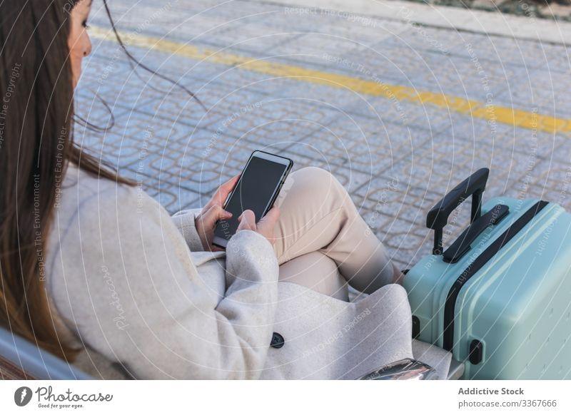Anonymer Oman wartet auf Zug und benutzt Telefon Frau Station Handy reisen benutzend Smartphone Feiertag Koffer Eisenbahn Bank Verkehr Terminal Transport