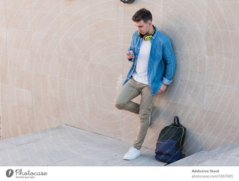 Schüler mit Kopfhörern surft mit einem Smartphone an der Wand lehnend Browsen Rucksack benutzend Bildung klug Mann Apparatur Campus Gebäude Hochschule Surfen
