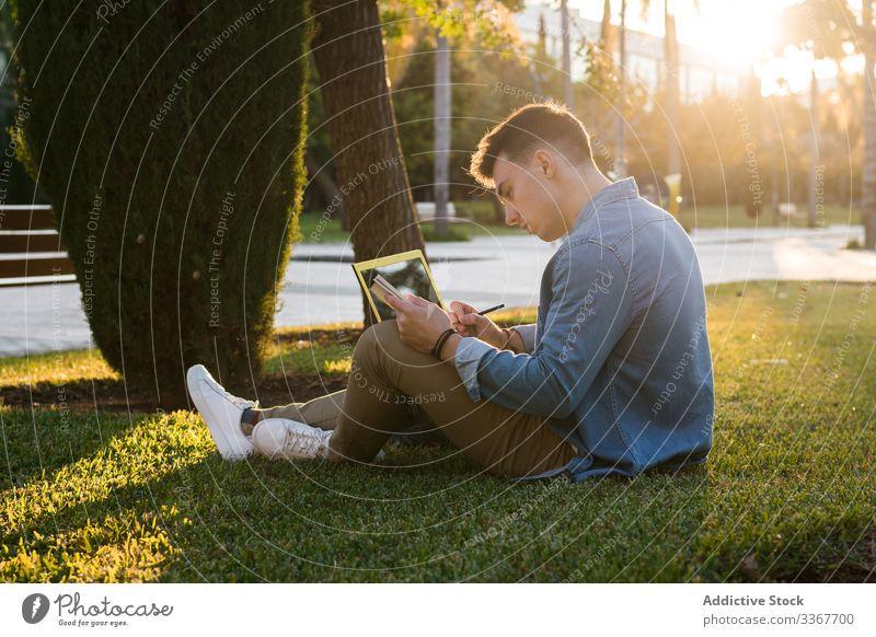 Student mit Rucksack beim Tippen auf Laptop und Notizblock im Park an hellem Tag Schüler Gras Computer Bildung benutzend studierend Universität lässig Lernen