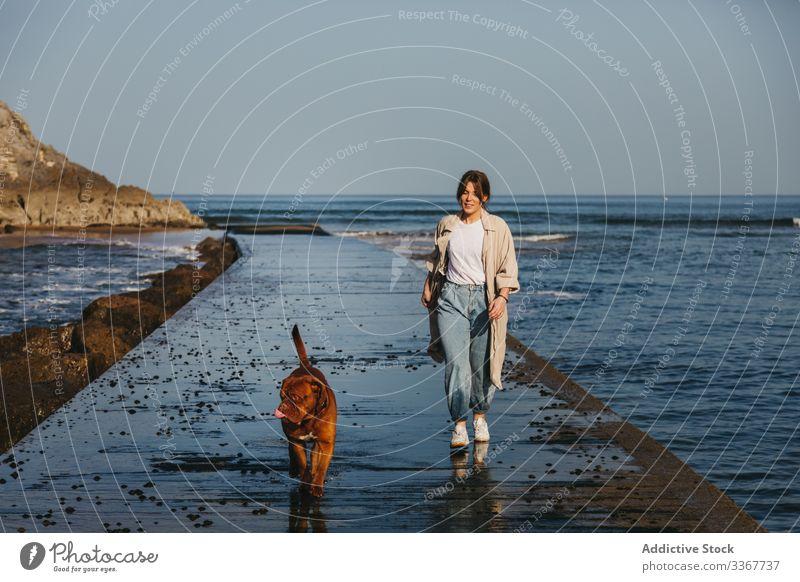 Frau mit Hund beim Spaziergang entlang der nassen Mole gegen ruhiges Meerwasser und felsige Küste bei sonnigem Wetter Pier MEER Wasser Begleiter frisch Haustier