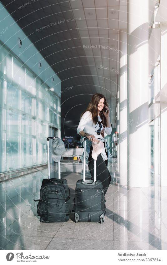 Ruhige Frau telefoniert am Flughafen sprechend Telefon Surfen benutzend Gepäck Urlaub Abheben Ankunft Abenteuer Tasche warten Smartphone Verzögerung Öffentlich