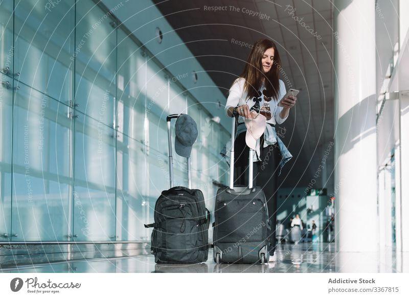 Ruhige Frau telefoniert am Flughafen Telefon Surfen benutzend Gepäck Urlaub Abheben Ankunft Abenteuer Tasche warten Smartphone Verzögerung Öffentlich