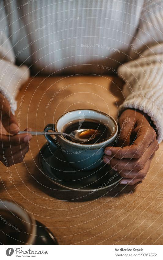 Anonyme Frau mit Kaffeetasse im Café Tasse Hand Erwachsener Person Sitzen genießend frisch heiß gebraut Becher trinken Getränk schwarz Tisch hölzern Kantine