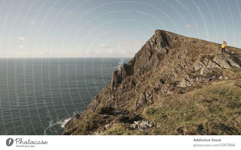 Unerkennbare fF Tourist nachdenken Natur Frau genießen Landschaft MEER Klippe Küstenlinie Schönheit Himmel Freiheit Feiertag reisen Erholung Lifestyle Urlaub